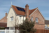 House fitted with solar panels on pitched roof, England, UK