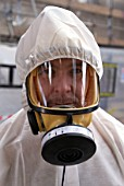 Asbestos Removal. Man in full protective clothing, United Kingdom