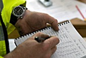 Construction manager writing time sheet on notebook
