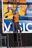 Worker putting up new billboard, UK