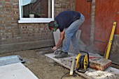 Man cutting paving slabs with cutter