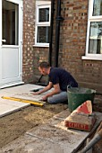 Man laying paving slabs in back garden