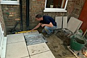 Man using level laying paving slabs in back garden