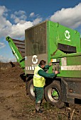 Man operating composting plant at site for recycling food and garden waste, Suffolk, UK