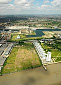 Aerial view of ExCel Exhibition Centre on Royal Victoria Dock and Barrier Point, a landmark housing development by Barratt, London Docklands, Thames Gateway, UK. A large plot visible on the side of the building.