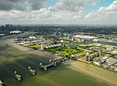 Aerial view of the Thames Barrier, ExCel Exhibition Centre on Royal Victoria Dock, Barrier Point, a landmark prestige housing development by Barratt, Tradewinds Barratt development, The Millennium Dome and Canary Wharf in the background. London Docklands, Thames Gateway, UK.