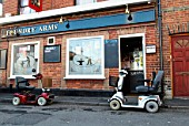 mobility scooters parked up outside a pub, Colchester, UK