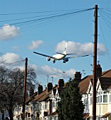 Aeroplane flying over rooftops near Heathrow Airport, London, UK