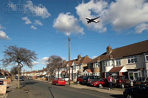 Aeroplane flying over rooftops near Heathrow Airport London UK