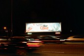 Advertising hoarding lit up at night next to busy road, London, UK