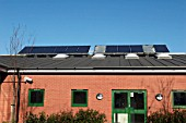Solar panels on a school roof, two of which have been vandalised, Ipswich, Suffolk, UK