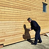 Wood staining weatherboarding on the side of a building