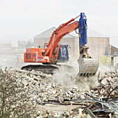 Excavator clearing a demolished site to make way for a paper recycling plant in Kings Lynn, Norfolk, UK