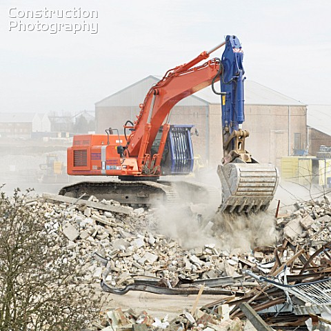 Excavator clearing a demolished site to make way for a paper recycling plant in Kings Lynn Norfolk U