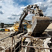 Loading construction site rubble into a separating machine at a construction materials and recycling plant, Greenwich, South-East London, UK