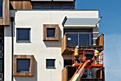 Wooden cladding being nailed onto a balcony frame of new apartments, Southend-on-Sea, Essex, UK
