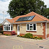 Solar heating panels on a bungalow roof, Clacton-on-Sea, Essex, UK