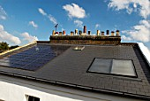 Photovoltaic roof panels and thermal solar panels on roof of Victorian house, Camden Town, London, UK