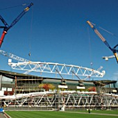 Two cranes work in tandem to lift roof trusses on to fixed roof of Centre Court, All England Lawn Tennis Club, Wimbledon, London, UK, 2008