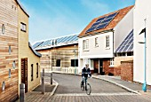 Man cycling. Sustainable eco-friendly houses. Eco Town, England, UK.