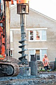 Auger drill rig drilling foundations on housing development, UK