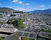 Traditional Architecture of the Old Town of Lijiang, with ancient rooftops. Yunnan Province, China. Yulong Mountains in Background. UNESCO World Heritage.