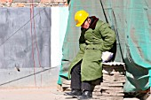 A construction work sleeping during a break on a building site in Beijing.