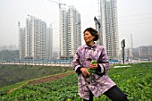 A local farmer picks crops as new residential housing is constructed in outer Chongqing.