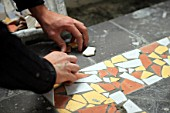 Worker arranging tiles for a mosaic
