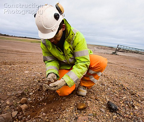 Man examining soil on brownfield site UK
