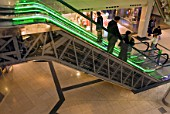 Escalator with lights and people, shopping centre, UK