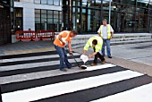 Workmen pouring paint onto new pedestrian crossing, Shudehill, Manchester, United Kingdom