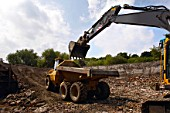 Crawler excavator loading articulated dumper