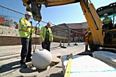 Outdoors stone seating being placed into correct area by workmen using mobile crane, Mablethorpe, Lincolnshire, UK