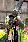 Construction worker pouring concrete, London, UK
