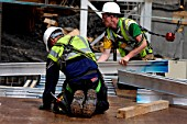 Construction workers laying plywood flooring, London, UK