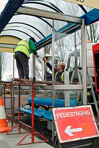 Workmen repairing vandalized bus shelters