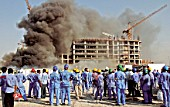 Al Mumzar industrial area. Labourers watch their building under construction hit by fire, Dubai, United Arab Emirates, October 22, 2006.