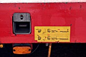 Yellow instruction notice on side of red articulated trailer.