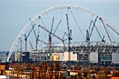 New Wembley Stadium under construction in January 2005, looking at the arch and cranes across rooftops from the south at dusk, London, UK