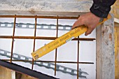 Carpenter using level with wood and rebar