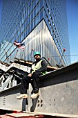 A worker sits on Survivors Stairway with 7WTC in the background, Lower Manhattan, New York City, USA