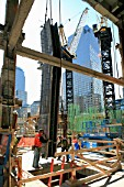 A shiny new steel column is lowered into a concrete footing at Tower One site, Lower Manhattan, New York City, USA