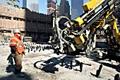 Worker by drill rig on Tower Three site, Lower Manhattan, New York City, USA