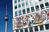 Soviet era murals on office building in former East Berlin with television tower to rear, Germany