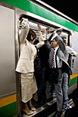 Paassengers try to fit inside very overcrowded railway carriage during morning rush hour in Tokyo 2008