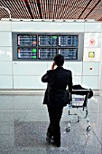 Businessman waiting in departure lounge, Beijing Airport, China