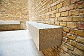 Simple stone bench  seaating and brick wall within Egyptian courtyard room of newly renovated Neues Museum in Berlin, Germany, 2009 Architect David Chipperfield