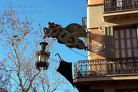 Detail of one dragon and lamp and umbrella in Las Ramblas Barcelona Spain