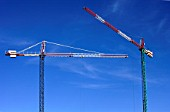 View of two cranes in a clear blue sky